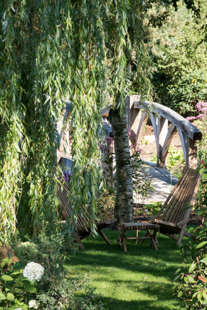 The bridge and willow seating area near the swimming pond